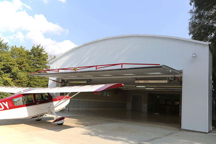Red plane outside hanger with hydraulic door